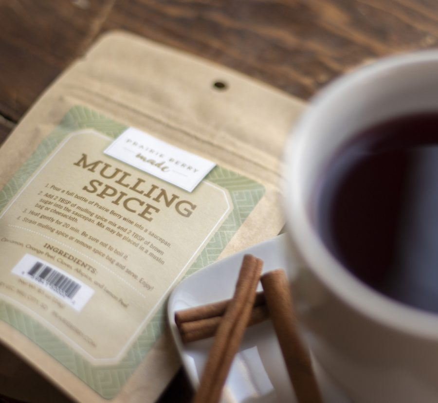 A packet of Prairie Berry Made Mulling Spice next to a mug of mulled wine